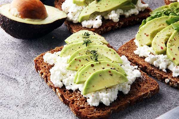 Tostada integral untada con queso crema y lonchas de aguacate por encima, salpimentadas con pimienta multicolor y una ramita de tomillo
