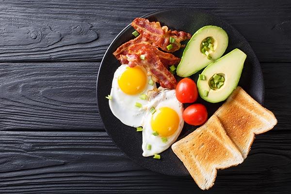 Aguacate, dos huevos fritos, varias lonchas de bacon, tomates cherry y un par de tostadas de pan