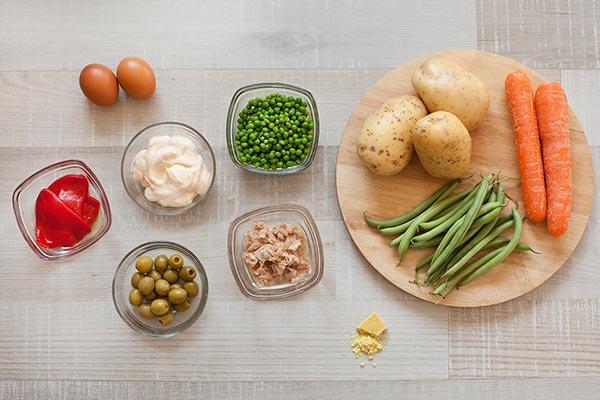 Ingredientes ensaladilla rusa: Zanahorias, aceitunas, pimientos de piquillo, judías verdes, zanahorias, huevos y mayonesa