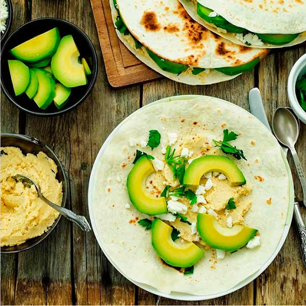 Corn tortillitas with slices of avocado, a little hummus, feta cheese, and fresh parsley